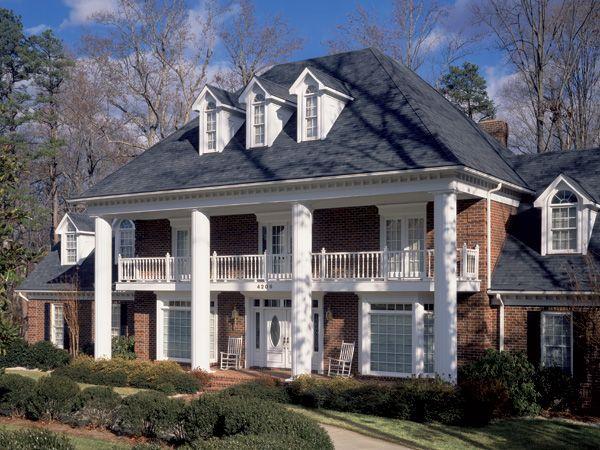 Exterior de casa típicamente americana con molduras decorativas en columnas y marcos de ventanas.