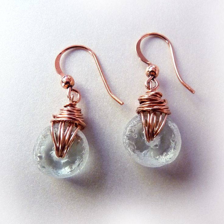 Fancy and fun. Eyecatching dangle earrings created from recycled bottle glass with copper wire wrapping. The recycled glass beads have a frosty matte finish around the edges and sparkling flat sides.