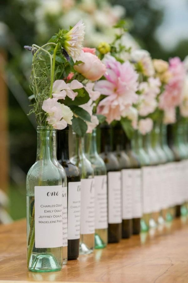 Use wine bottles as vases with printed seating charts in lieu of labels for a…