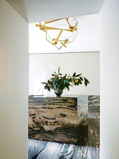 House tour: a Milanese palazzo beautifully stripped back to its roots: Brazilian marble in the kitchen; brass light by de Cotiis.