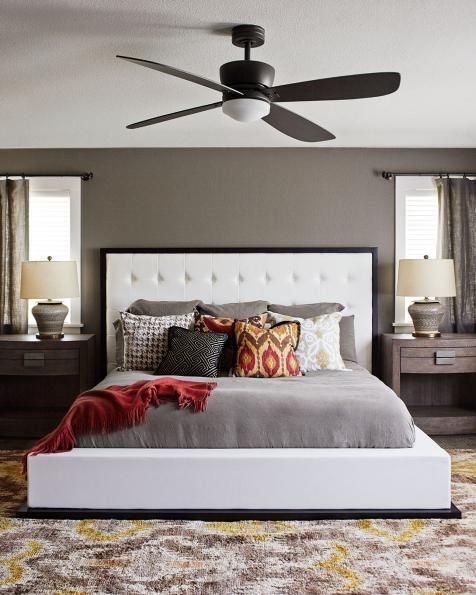 This transitional bedroom contains a beautiful blend of masculine and feminine touches. The window treatments and furniture placement create symmetrical balance, while an assortment of boldly patterned pillows adds interest. The large, white leather bed grounds the space and gives it visual weight.