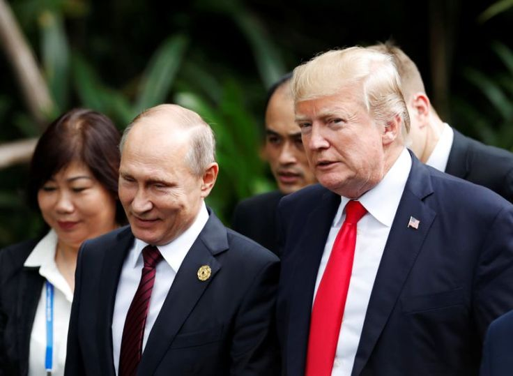 President Donald Trump and Russia's President Vladimir Putin attend a photo session at a summit in Vietnam on Saturday. (Jorge Silva / Reuters)