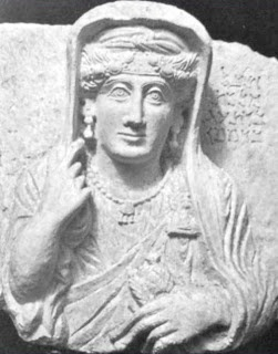 Malkat died between 150-170 CE.  She holds her veil with her right hand, raising it to collarbone level, and in her left hand loosely grasps a spindle and distaff. She wears a floral-design headband, a head-chain made of round stones and a knotted turban underneath a veil.  The jewellery displayed includes a brooch, dumbbell earrings, and a necklace of stones with an oval pendant, which itself has three smaller pendants.