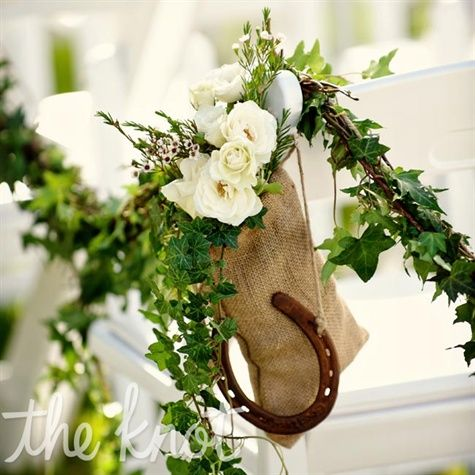 Garlands of ivy, miniature bunches of white flowers and hanging horseshoes marked the side of the aisle.