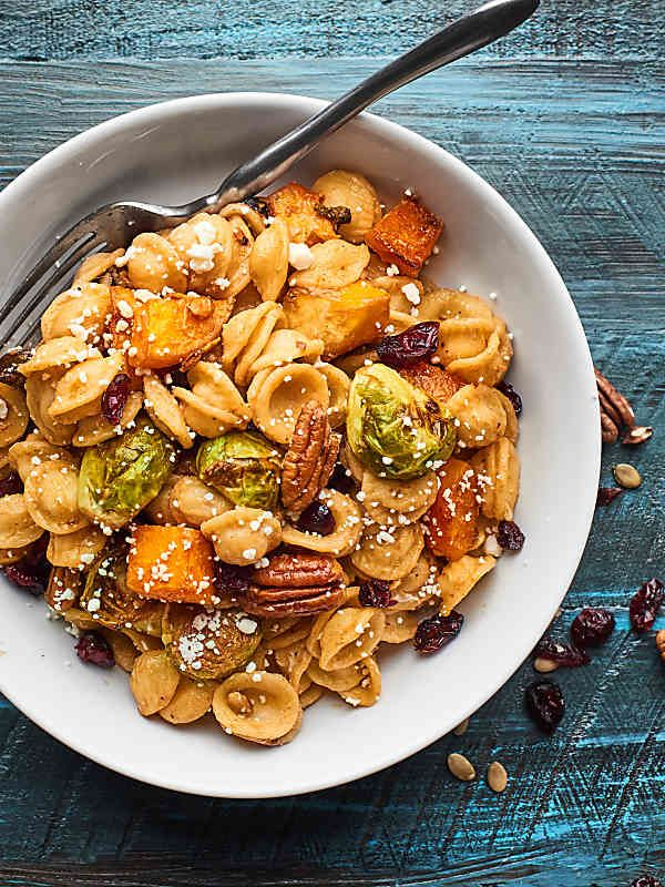 This Easy Roasted Fall Vegetable Pasta Recipe is full of roasted butternut squash and brussels sprouts, pecans, pumpkin seeds, goat cheese, and dried cranberries! showmetheyummy.com #fallpasta #roastedvegetables