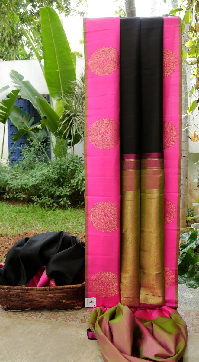 The base of this kanchivaram silk is in black. The border is a thick band of pink with large bhuttas in gold zari and a moss green selvedge, while the pallu is in moss green and purple with gold za…