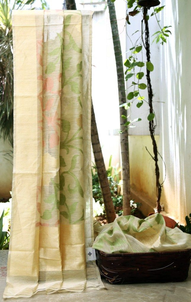THIS OFF WHITE LINEN HAS A PALE RED AND GREEN COLOURED FLORAL DESIGN WITH A HINT OF GOLD AND SILVER ON THE BODY. THE TEXTURED GOLD AND WHITE BORDER COMPLIMENTS ITS SIMPLICITY