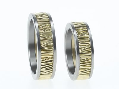 Het middendeel van deze ringen is van prachtig geelgoud waarop met de hand een structuur is aangebracht. Strakke ringen blijven het door de toevoeging van de zakelijke tianium zijkanten. Bedenk eens hoe de ringen zijn met een gouden middendeel en zwarte zijkanten.... Ook heel vet!