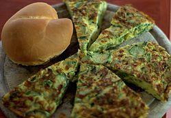 Cucina friulana - frittata con le erbe di campo e un cornetto,classica forma di pane friulano