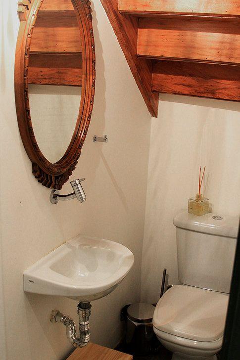 Lavabo reformado sob escada de madeira. Espaço sobre a escada bem aproveitado. Lavabo pequeno. Cuba suspensa, torneira de parede. Espelho com moldura de madeira.