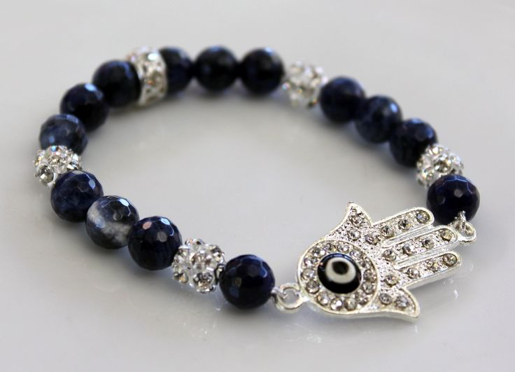 Hamsa Bracelet B088  $32 I designed this bracelet with Faceted Sodalite Gemstone Beads, Dimanté Silver Plated Metal Spacers and a Dimanté Hamsa with Eviled Eye in the centre.  Easy to get on and off, this is a great piece to wear alone or stacked with other bracelets in your wardrobe.  Made with two layers of sturdy elastic cord, the bracelet will comfortably fit an average size wrist.  Length – 18cm, excluding size of Hamsa – 3.5cm.