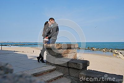 Couple kissing on a platform next to the Black Sea