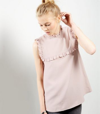 """Keep your work wardrobe elegant but stylish with this mid pink shell top. Pair with skinny jeans and strappy silver heels to finish.- Frill trim- Sleeveless design- Funnel neckline- Casual fit that is true to size- Soft finish- Saga is 5'8.5""""/174cm and wears UK 10/EU 38/US 6"""