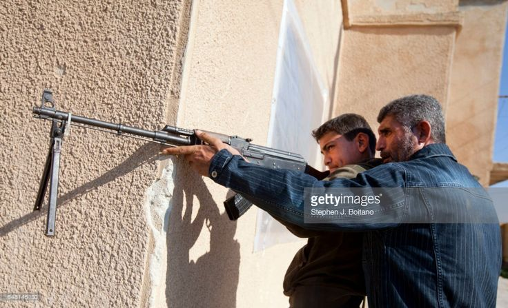 Kamel, right, teaches Mohamad, age 16, how to shoot at a Free Syrian Army youth soldier training camp in Syria.Their ages range from 14 to 18 and they spend several weeks working on fighting skills before being sent to the frontline.