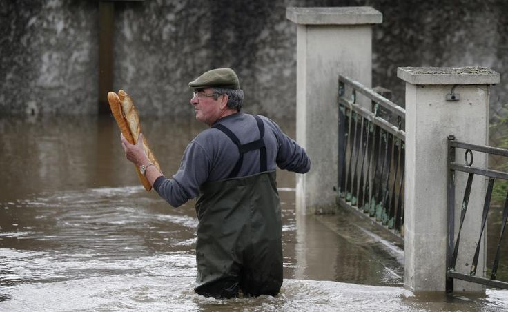 Reuters / Wednesday, June 01, 2016 A resident brings French baguettes to his mother's flooded house after heavy rain falls in Chalette-sur-Loing Montargis, near Orleans, France, June 1, 2016. REUTERS/Christian Hartmann