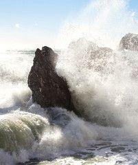 wave crashing on the beach against big rock
