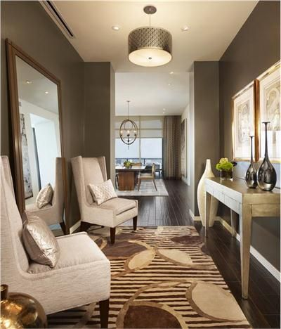 Love everything about this hallway...the huge mirror, the chairs, the table, the dark hardwoods