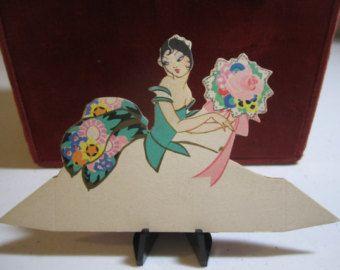 Die Cut oro dorato signora graziosa con scheda del posto di Buzza 1920 inutilizzati in abito elaborato che tiene un grande mazzo di fiori