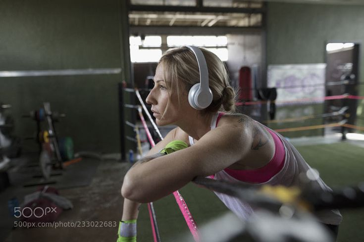 Female boxer listening to music with headphones in boxing ring at gym by HeroImages
