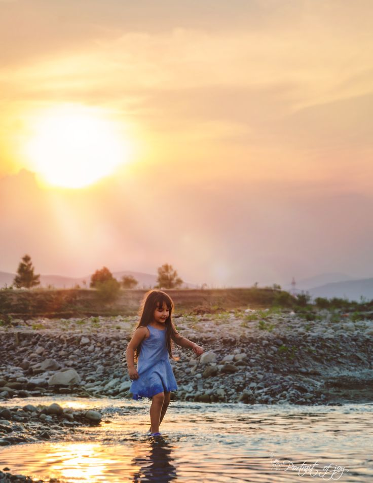 Little girl playing in the river at sunset