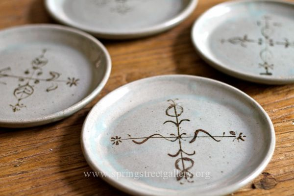 Small celadon plates with vodoo-inspired designs