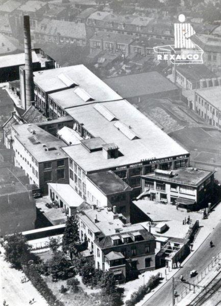 Luchtfoto van Kledingindustrie H. Smits & Co. (Rexalco) aan de Parallelweg. Op de voorgrond de villa van de familie Smits, met groene omheining. Deze villa heeft na de oorlog nog dienst gedaan als de Almelosche Radiocentrale. Vanaf de jaren '60 zat Klokkenfabriek Warmink (WUBA) in dit complex, schuin tegenover het station. Helemaal bovenaan op de foto zijn de huizen aan de Dijkstraat nog te zien.