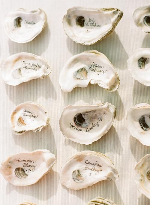 Pretty calligraphed oyster shells make such a unique escort card display | Brides.com