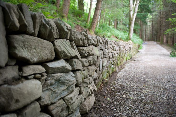 A Retaining wall is often used when a road is made on a hill. After time, they can begin deteriorating. I was tasked with rebuilding 100' of stone walls.