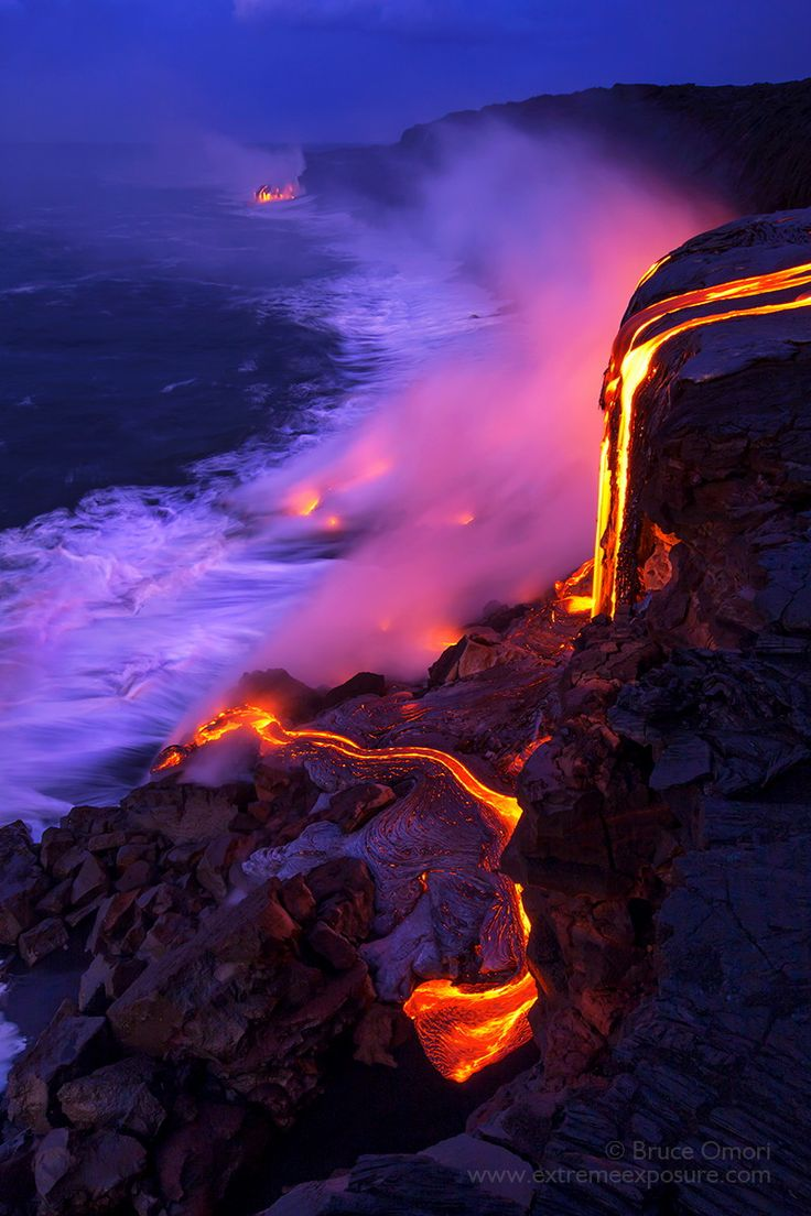 Molten lava cascades over a 30 foot cliff, creating new land at its base, Kilauea, Hawaii, USA