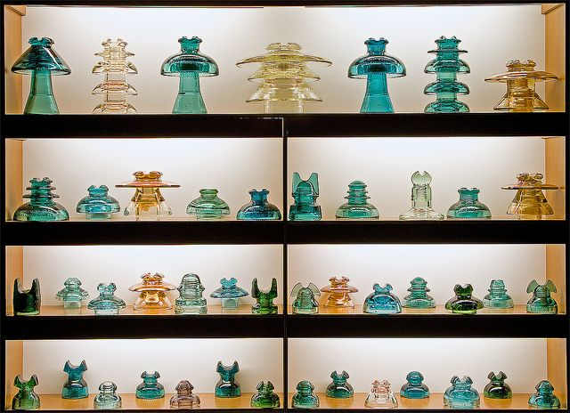 """Matt Weldon's collection of glass pintype power insulators in a display cabinet. According to Matt, """"[t]hese insulators were used for high voltage distribution and are the largest and heaviest glass pintype insulators made in North America.""""  For more information, see monon738's flickr stream."""