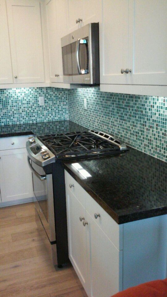 Superior Butterfly Green Granite Countertops With A Square Edge And Blue Glass Tile  Mosaic Backsplash.