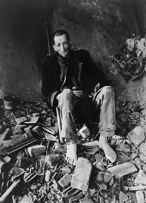 French prisoner at Nordhausen Concentration camp amid prison rubble waiting for an ambulance to take him to a hospital after liberation by First U.S. Army on April 11, 1945.