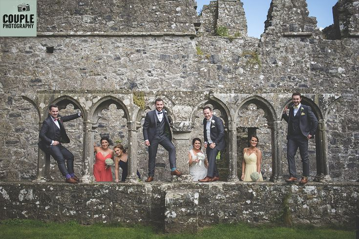 The bridal party pose under the arches at the gorgeous Fore Abbey. Weddings at Mullingar Park Hotel by Couple Photography.