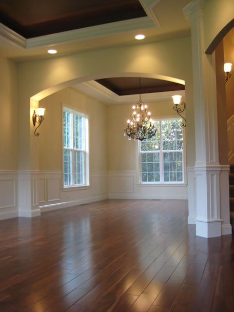 What a beautiful and elegant dining room. Love the  lighting fixtures, windows, and floor as well. Formal dinning room separation by arch....good flow of rooms.