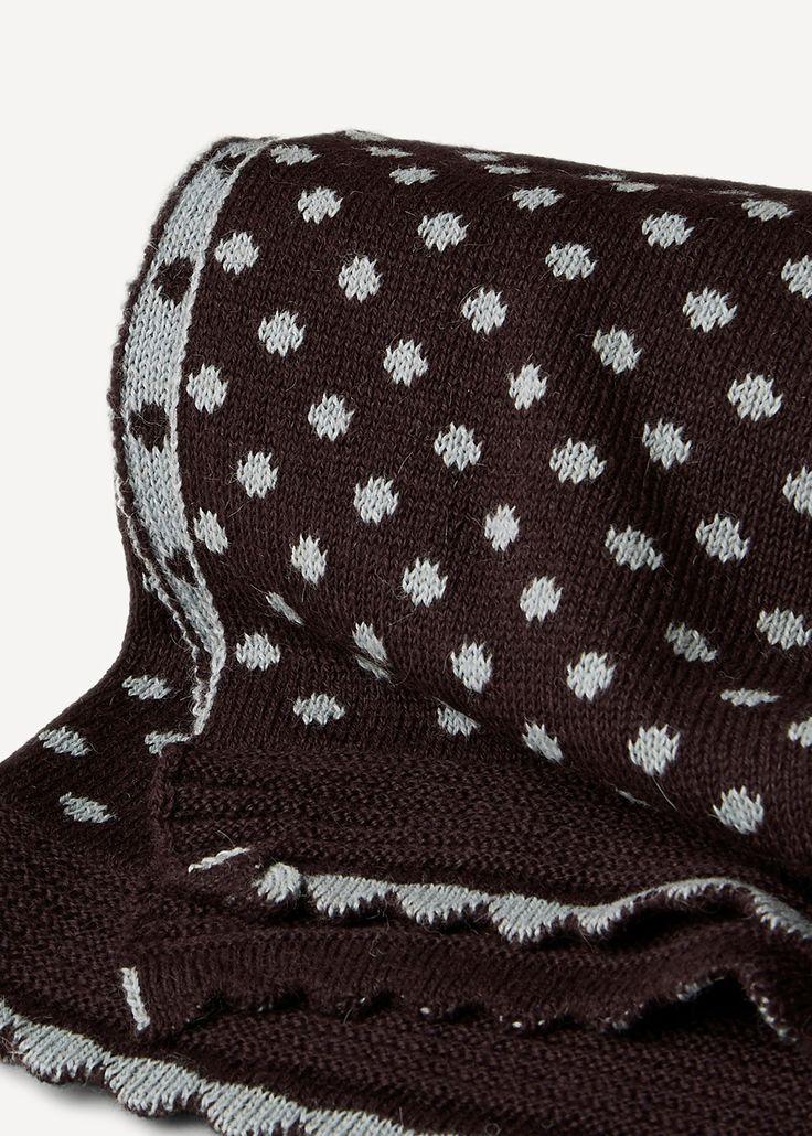 Et strikket kast eller pledd, du bestemmer bruken! Kastet er dobbeltstrikket som gjør at fargene på det prikkete mønsteret er motsatt på de to sidene. En elegant, bølget kant rammer inn kastet. Størrelse: ca. 160 x 85 cm