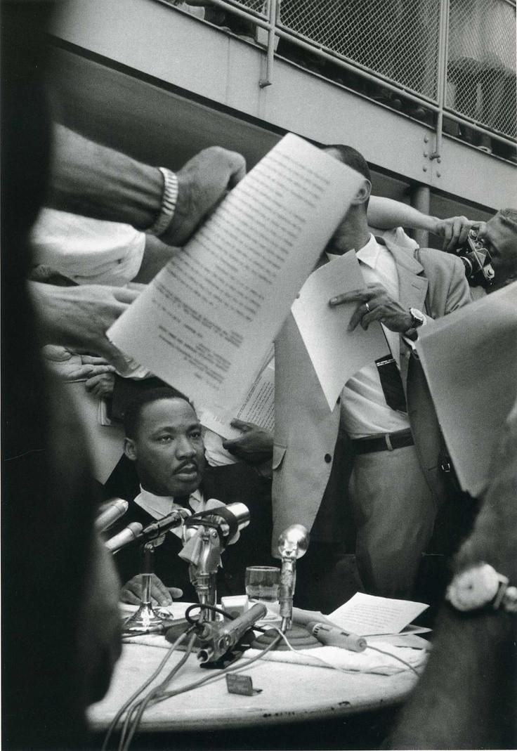Martin Luther King surrounded by journalists after giving a speech in Birmingham, Alabama 1963 by Ernst Haas.