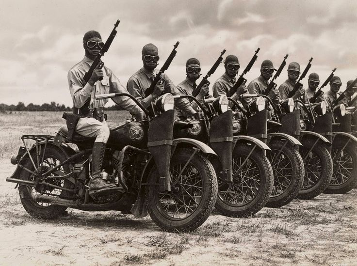 U.S. soldiers on Harley-Davidson WLA motorcycles, equipped with unloaded Thompson submachine guns during WWII.