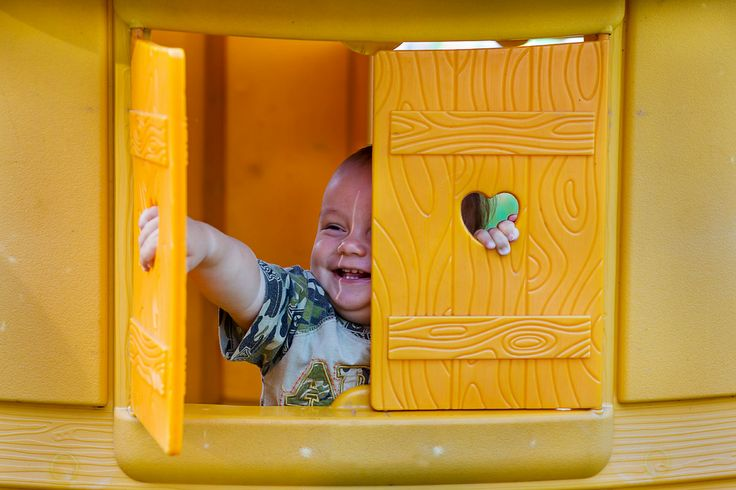 happy kid in a yellow children's house