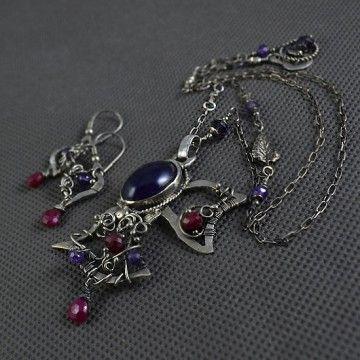 Komplet stylowej biżuterii -  duży, misterny naszyjnik i kolczyki. Wykonany techniką wire-wrapping z oksydowanego i polerowanego srebra (próba 999,930). Sercem wisiora jest wysokiej jakości  kaboszon ametystu połączony z fasetowanymi oponkami i łezkami soczyście wybarwionych rubinów.