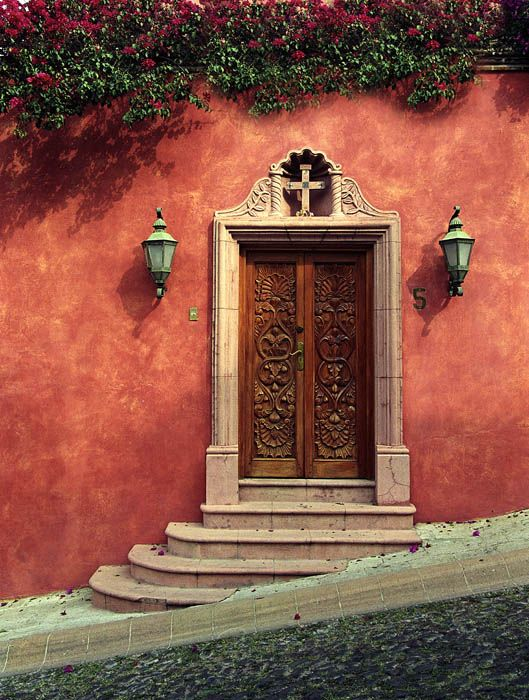 Absolutely stunning, love the colors and texture of wall, angle of stairs, light fixtures, engraving of the wood door, and architecture of door frame.
