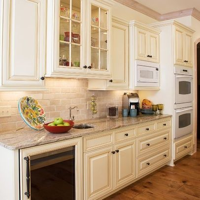 Cream subway tile and distressed kitchen cabinets cream for Kitchen cabinets distressed white