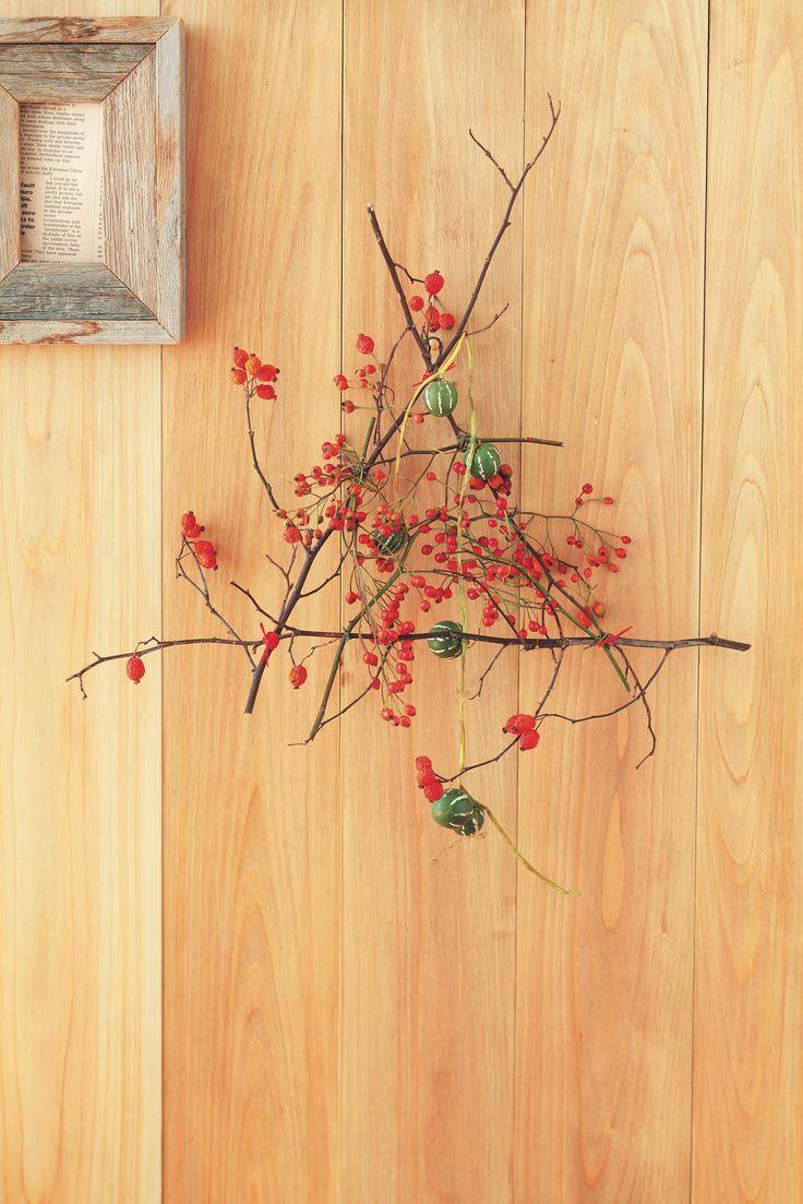 赤い実のついた枝を三角形に組んで、ツルや実ものをプラス。壁やドアの飾りに。/身近な器でやさしい花レッスン(「はんど&はあと」2013年11月号)