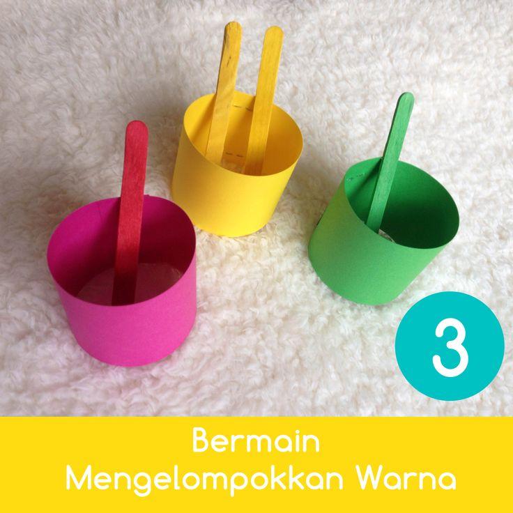 Bermain Mengelompokkan Warna   Cara Bermain:  1. Ajak anak untuk mengenali masing-masing warna stik eskrim dan 'keranjang' yang Anda buat dari gulungan tissue. 2. Minta anak untuk memasukkan stik eskrim ke keranjang yang warnanya sama. 3. Setelah itu, Anda pun bisa mengajaknya berlatih menghitung jumlah stik eskrim yang ada dan mulai memperkenalkan konsep lebih banyak dan lebih sedikit.