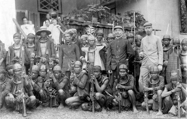 "A group of subdued headhunters, Nias ""a group of head hunters came to submit themselves"" Nias, Northern Sumatra, ca 1920"