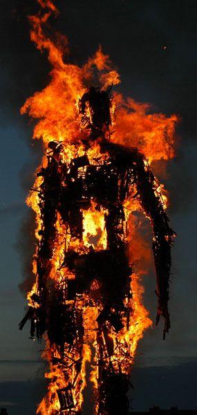 "bBrning Antony Gormley sculpture in Penny Wood's ""Exodus"""