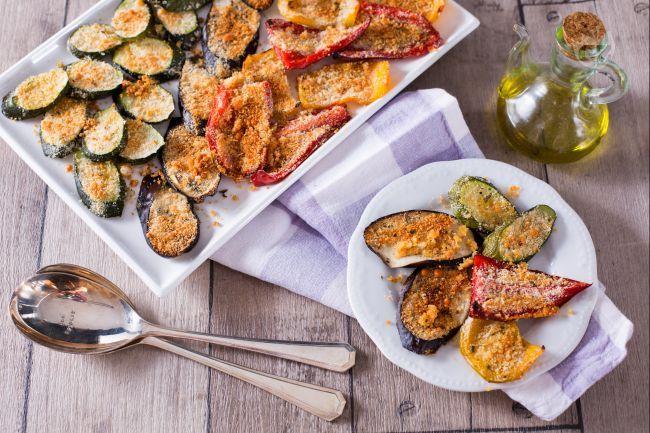 Le verdure gratinate al forno con panatura di pangrattato, parmigiano e origano sono un contorno versatile, leggero, colorato e ricco di sapore.
