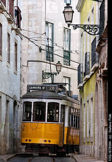 The famous electrico Tram 28 passing through a narrow street in Alfama district, Lisbon, Portugal