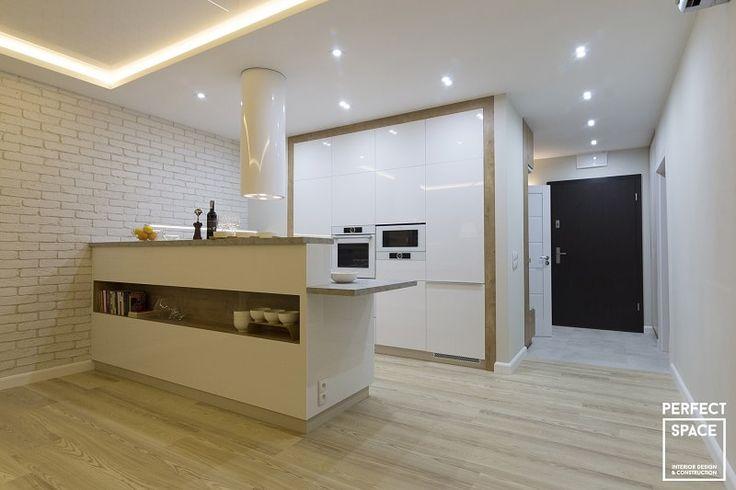 Kuchnia otwarta na salon. Meble kuchenne na wysoki połysk, z zabudowanymi sprzętami AGD.