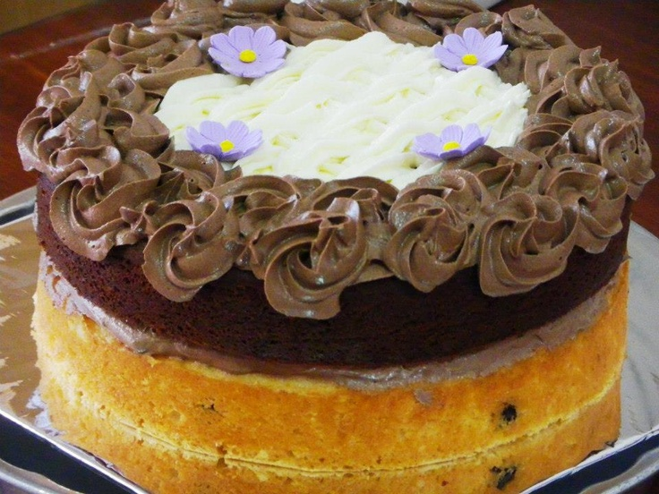 Two Layer Cake, the bottom is a Pin Up's Vanilla Chocolate Chip Cake, on top of which is our Chocolate Delight Cake. Centered in between is our Fluffy Chocolate Frosting. For the Complete Finish we did patches of Vanilla butter cream surrounded by chocolate butter cream flower patterns.