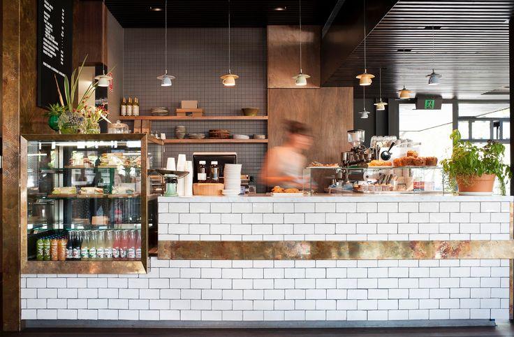 barra de azulejo blanco con cenefa en cobre y zona refrigerada. Lámparas fabricadas con tazas de desayuno.